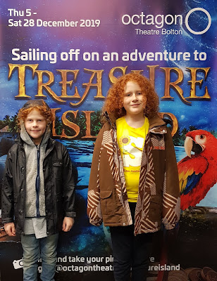 My two boys standing in front of large advertising board for Treasure Island