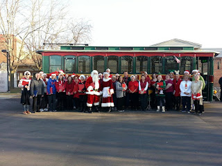 Santa, Mrs. Claus and a group of passengers on the Travel Plus Christmas Lights trolley in Sioux City