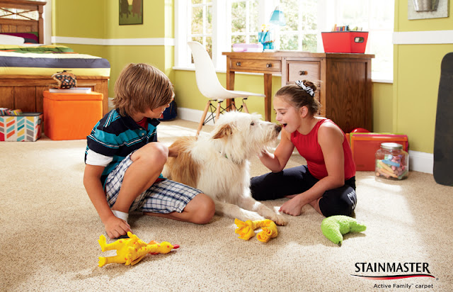Kids and their dog playing on a carpeted floor