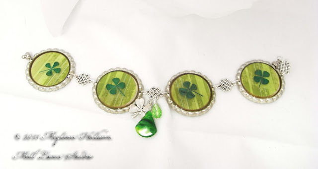 Bottle cap bracelet featuring green striped scrapbook paper with real dried 4 leaf clovers embedded in resin.