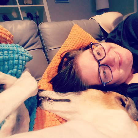 image of me from the shoulders up lying on the couch sideways, with my head next to Dudley the Greyhound's head
