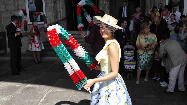 Invitada boda sosteniendo arco para el baile aurresku con canotier by malonsilla