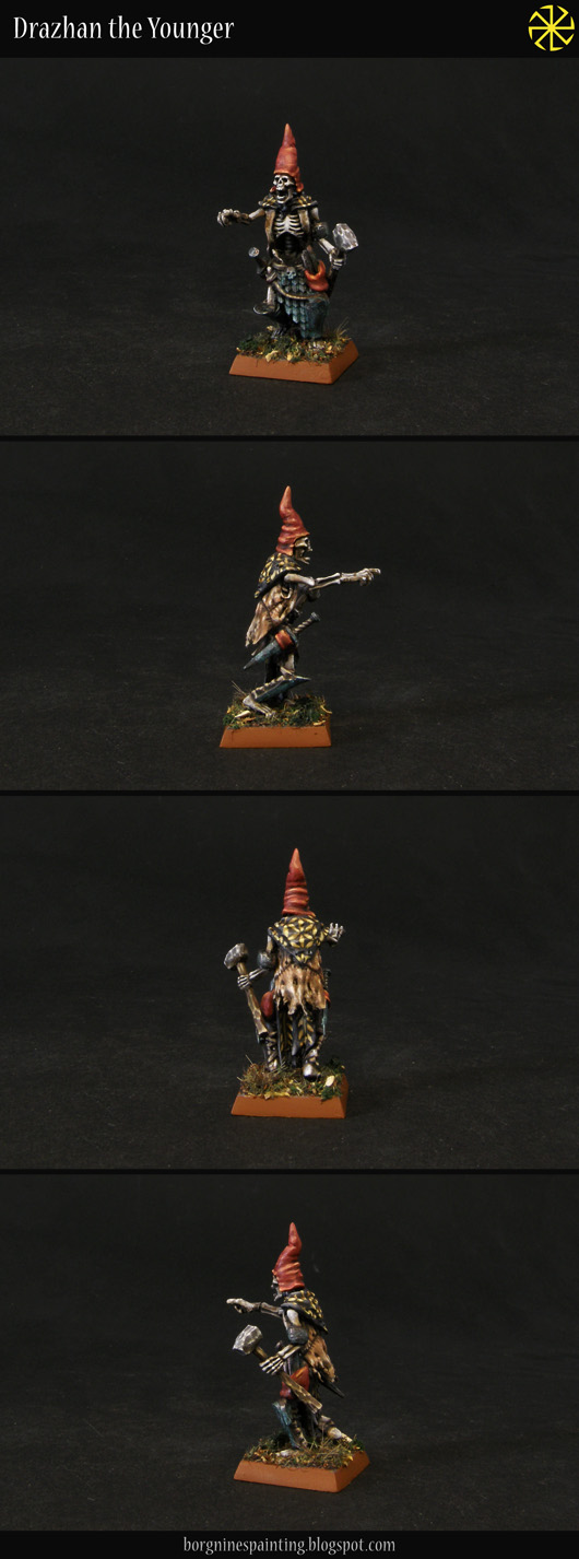 Painted, kitbashed model of a Tomb Kings Necrotect, converted to fit in a Vampire Counts army. He has a high, red hat, points something with his right hand and is carrying a hammer in his left hand. The miniature is visible from several angles.