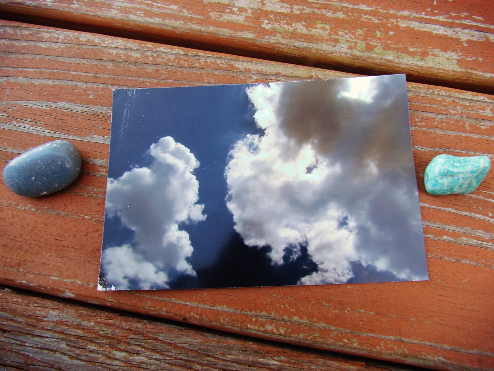 A flat lay with a cloud photograph, two gemstones, and a wooden plank background in mother nature