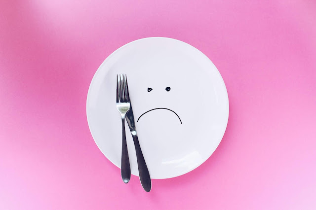 Empty plate with a knife and fork, and a sat face drawn on it