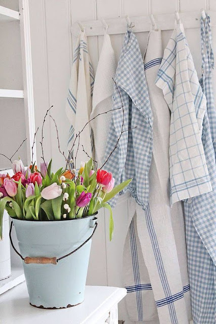 Beautiful pink tulips in tin bucket and blue and white kitchen dishtowels