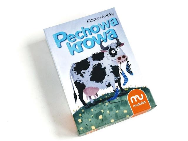 na zdjęciu pudełko gry pechowa krowa a na okładce krowa, trzymająca w pysku sznur na pranie z przyczepionymi do niego skarpetami