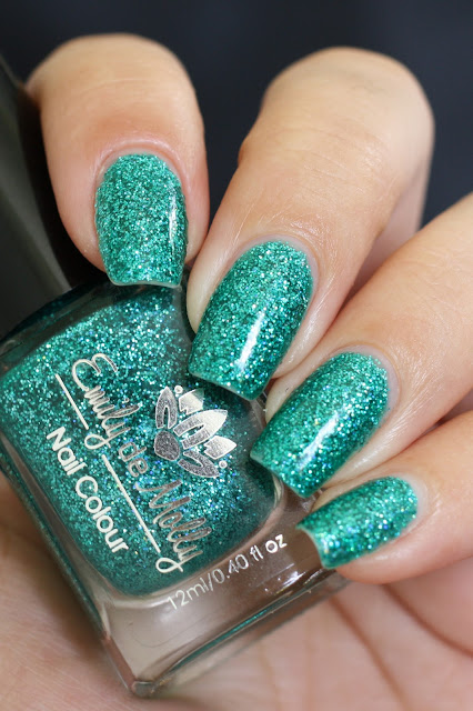 Long nails painted with turquoise glitter nail polish