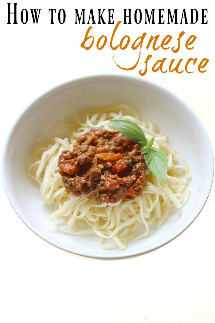 A white bowl of linguine pasta covered in bolognese sauce with a side sprig of fresh basil