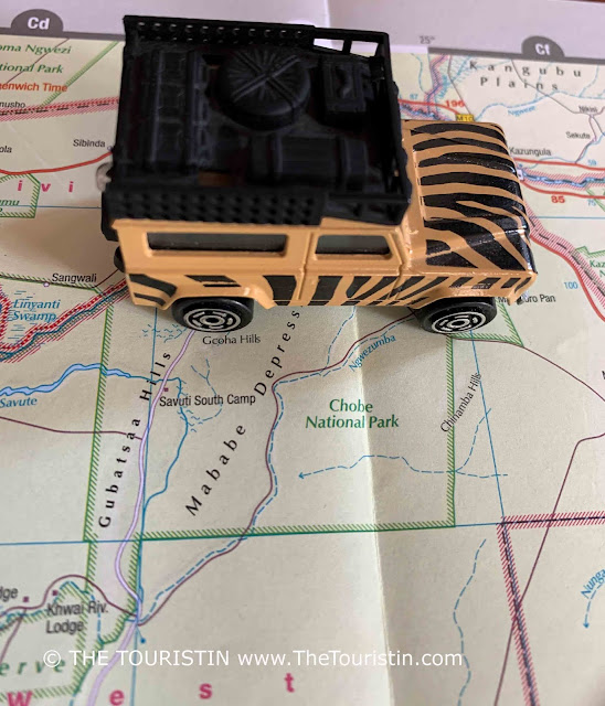 A beige and black painted toy Land Rover on a paper map next to the words Chobe National Park.