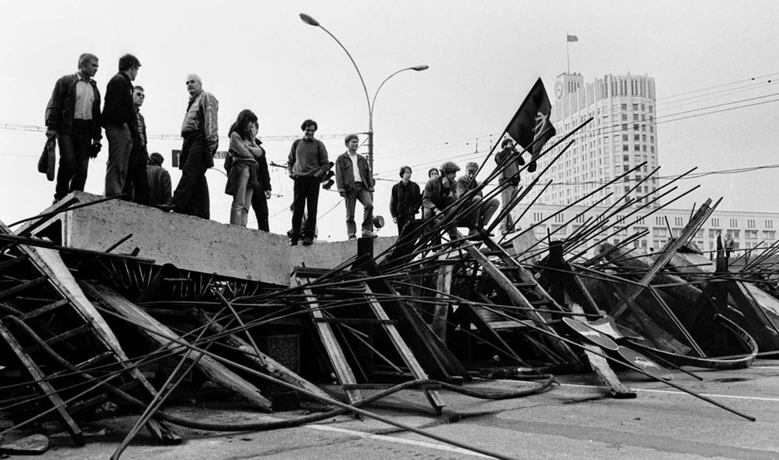 People stand on a barricade in front the Russian White House in Moscow on August 21, 1991.