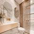 Banheiro branco e dourado com painel decorativo no box e armário revestido de porcelanato!