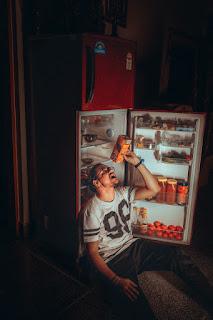 Man sitting in front of refrigerator drinking juice - via Unsplash: Chandler Mohan at https://unsplash.com/photos/eYzg_aaTkcU