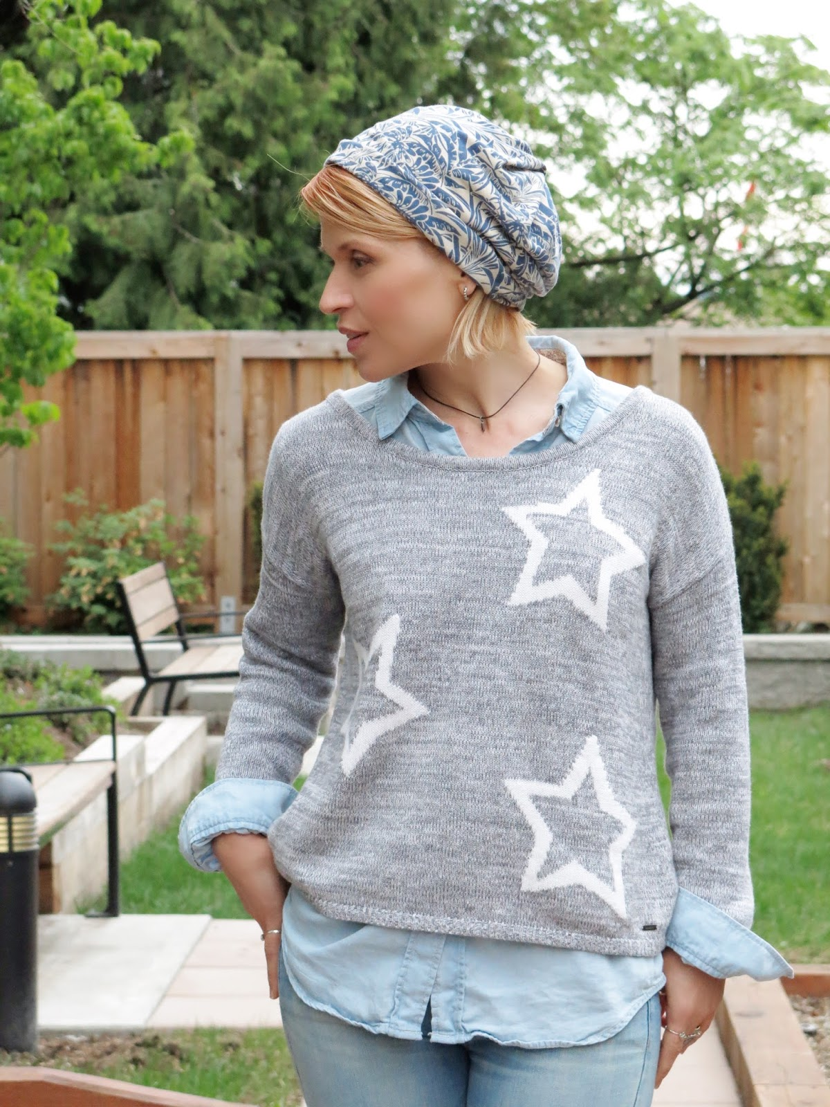 chambray shirt layered under a star-patterned sweater, and a floral jersey beanie