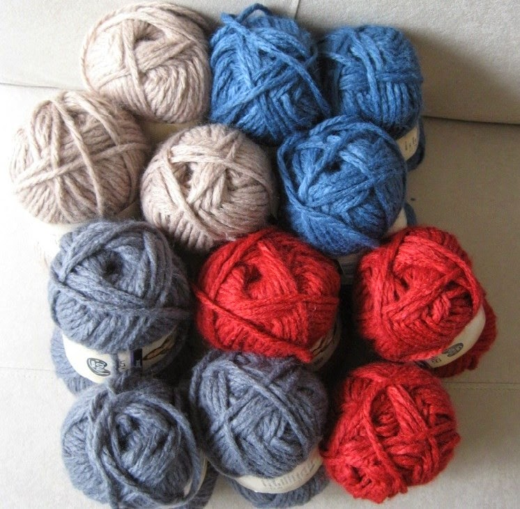 12 skeins of Moda Vera Shiver acrylic super-chunky yarn in four colours, three skeins of each colour comprising Camel natural, Denim blue, Burgundy red and Dark Grey. They are arranged so that they are in an upright position against each other and viewd from the top of the skein.