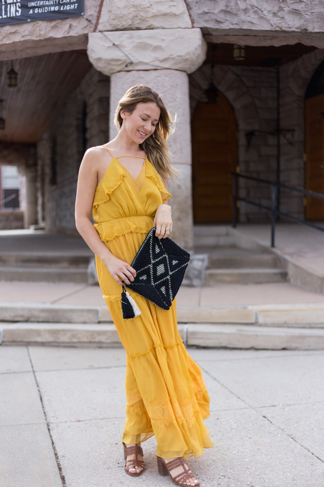 yellow summer maxi with black tassel clutch