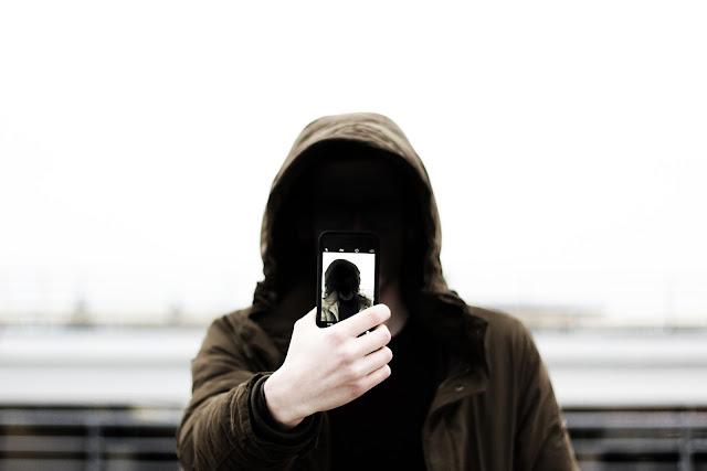 A imagem exibe um homem com o rosto coberto fazendo uma foto de si mesmo (selfie)