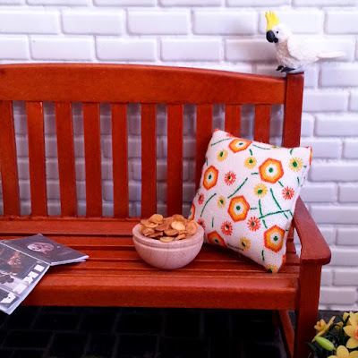 One-twelfth scale modern miniature wooden park bench in front of a white brick wall. On the bench is an IKEA catalogue, a bowl of chips and a white, green and orange cushion. On the pavers next to it is a pot of daffodills, and perched on the back of the bench is a cockatoo eyeing up the chips.