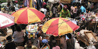 Shelter from the fierce sun in a packed market in Lagos, Nigeria. (Image Credit: ouzou Wizman / Flickr) Click to Enlarge.