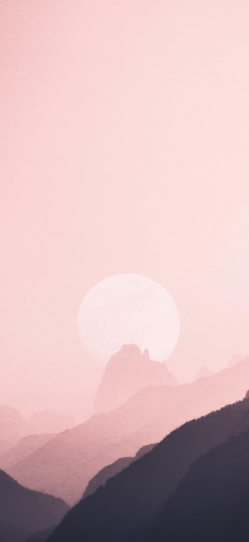 pale sun hiding behind mountains