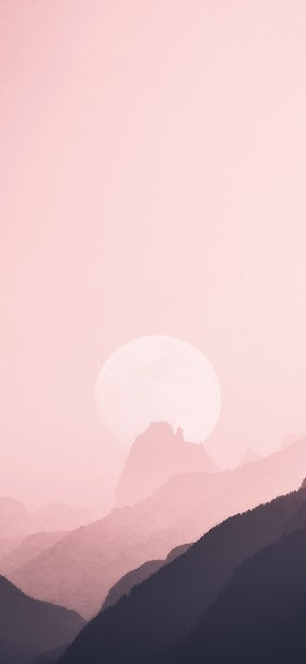 Pale sun hiding behind mountains wallpaper