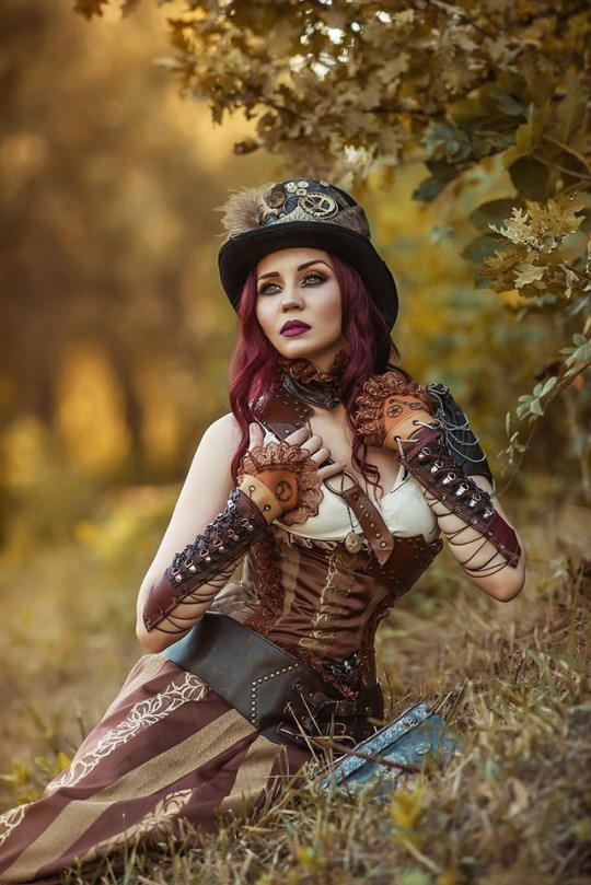 steampunk woman wearing cool gauntlets, hat, skirt, belt, corset and other steampun clothing.
