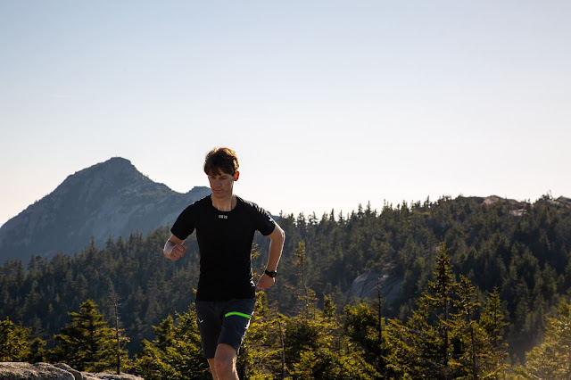 A young white man wearing the black GORE base layer short sleeve shirt runs towards the camera with the imposing peak of Mt. Chocorua and a forested mountain ridge in the background.