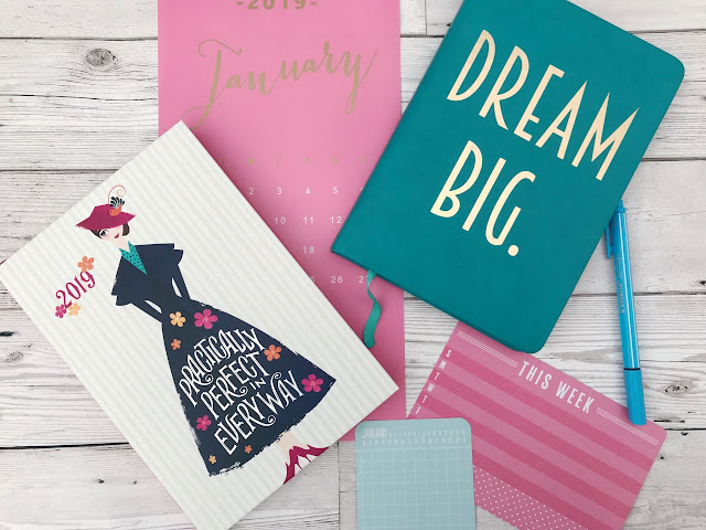 Flatlay showing a Mary Poppins diary, a January calendar, a book marked dream big, a pen and two small cards with one saying This Week and the other January