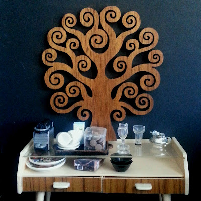 Modern miniature credenza in front of a black wall with a large wooden tree of life on it. On the credenza is a Nespresso machine, tray with cups, saucers, milk and a container of biscuits, next to two wine glasses, a water glass and a silver milk jug.