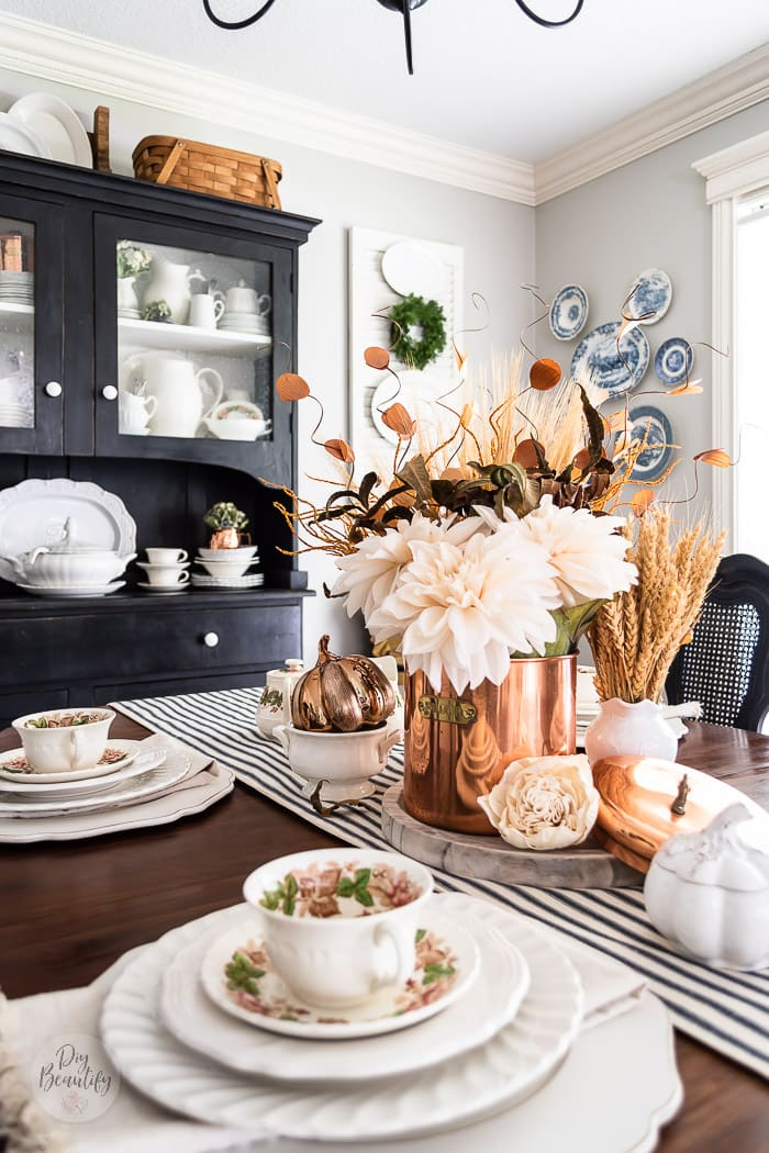 dining table fall centerpiece with cream dahlias in a copper canister, dried wheat stalks in white pitchers, ironstone and dried hydrangeas