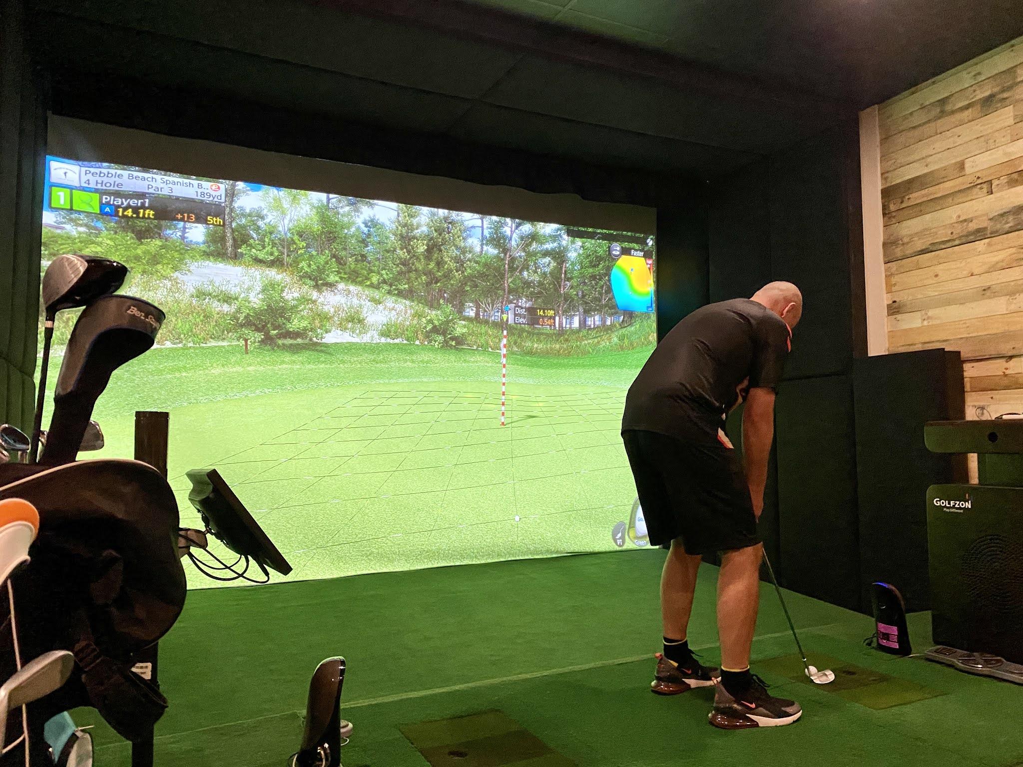man playing on a golf simulator