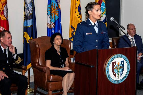 Layne Allemond speaks at a podium. Three people sit in chairs behind her.