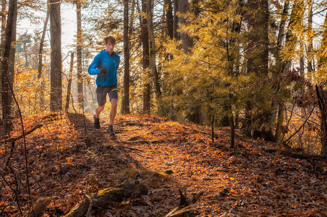 A young white male wearing a light blue jacket and grey shorts runs along a trail downhill towards the camera through sunny woods, surrounded by trees in golden autumn color.