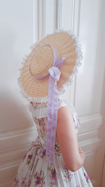 auris wearing a huge bergere hat with a purple ribbon and a floral dress
