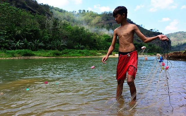Anak warga setempat sedang menjaring ikan di Sungai Oya