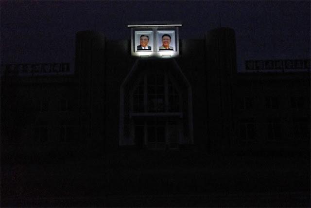 Vào ban đêm, hai bức ảnh trên được chiếu sáng, trong khi các ngôi nhà khác trong làng chìm trong bóng tối.