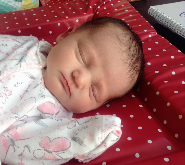 Image of newborn baby girl dressed in a floral sleepsuit and laid on a re polka dot pvc wipe clean changing mat