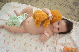 Ребёнок с плюшевым мишкой лежит на пелёнке