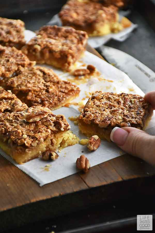 Pecan Pie Bars squares on a cutting board with a hand reaching in to pick one up