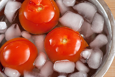 Submerging tomatoes in an ice bath