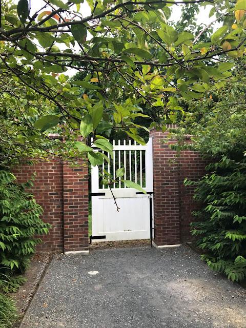 White garden gate between brick walls