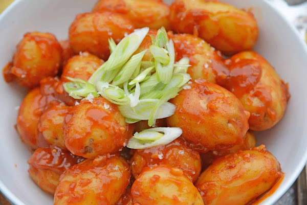 Close up top view of chile garlic potatoes in a white bowl.