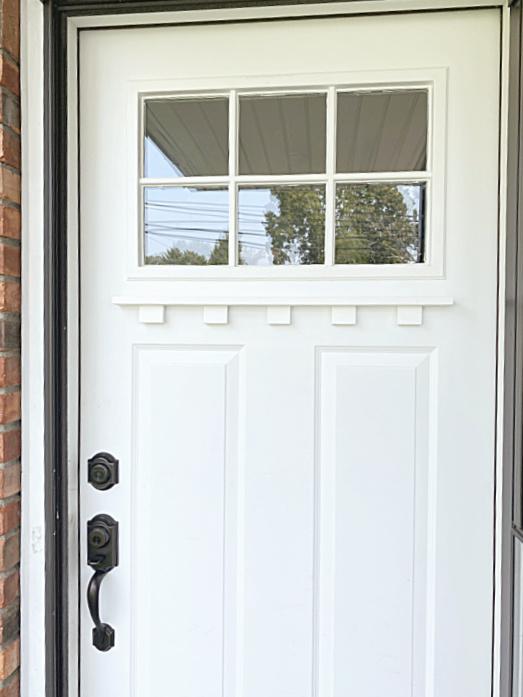 white front door with dentil shelf