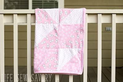 pink baby quilt hung over a railing