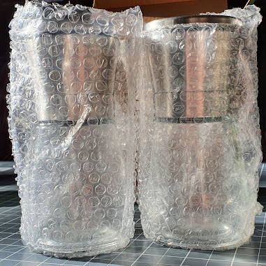 glass bodied, metal top half, salt and pepper pots still in bubble wrap
