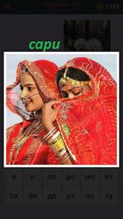 две девушки одеты в сари красного цвета закрывают свои лица