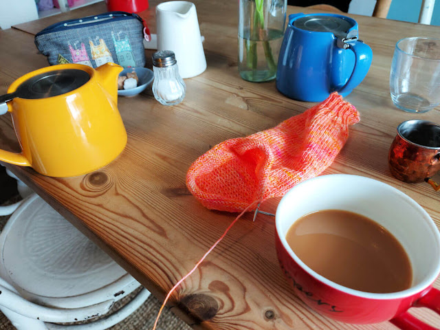 A wooden table with teapots, cups of tea, salt shakers, sugar in a bowl, a partly-knitted orange sock and a small accessories bag with houses