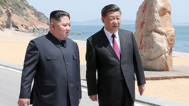 Image Attribute: Chinese President Xi Jinping, right, walks with North Korean leader Kim Jong Un during a May 7-8 meeting in Dalian in northeastern China's Liaoning Province. / Souce: Xinhua