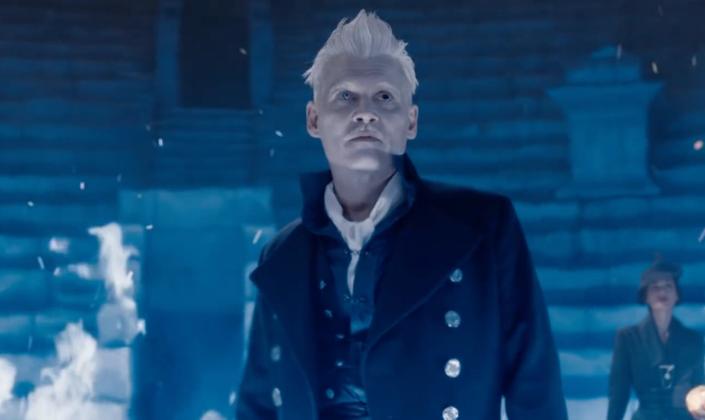 Imagem de capa: cena de Animais Fantásticos na qual Grindelwald, interpretado por Johnny Depp, com cabelos loiro-platinados e arrepiados, olhos heterocromaticos, diferentes um do outro, um branco e outro preto, com um bigode e um casaco preto cheio de botões, olha para cima, rodeado de chamas azuis em uma espécie de anfiteatro subterrâneo.