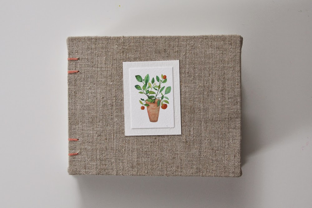 hand bound book with linen cover and potted orange tree